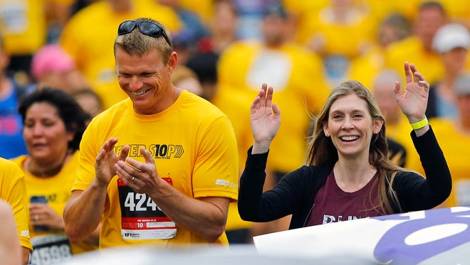 Alex Garwood, Director of the Tillman Foundation and Marie Tillman wave to family before finishing the 10th annual Pat's Run Saturday, April 26, 2014 in Tempe.