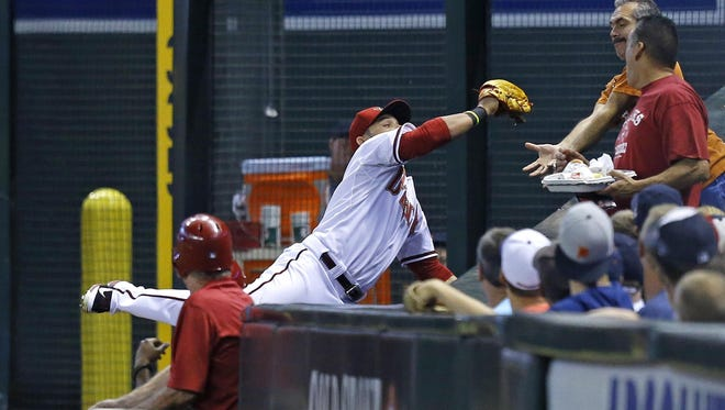 Arizona Diamondbacks right fielder Gerardo Parra (8) makes a catch on a foul ball by Detroit Tigers'  Eugenio Suarez (30) in the 2nd inning of  their MLB game at Chase Field Tuesday, July 22, 2014 in Phoenix.
