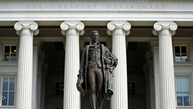 A statue of the first United States Secretary of the Treasury Alexander Hamilton stands in front of the U.S. Treasury.