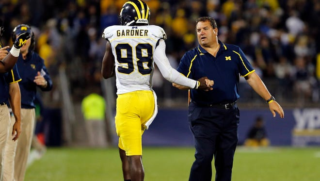 Michigan Wolverines head coach Brady Hoke greets quarterback Devin Gardner (98) after a touchdown in the third quarter against the Connecticut Huskies at Rentschler Field.