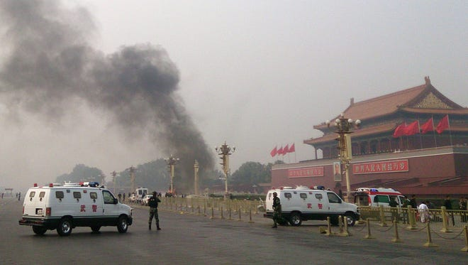 Police cars block roads leading into Tiananmen Square on Oct. 29 after a vehicle crashed and exploded in Beijing. Chinese Police said the three people who died inside the car were Uighurs from Xinjiang.