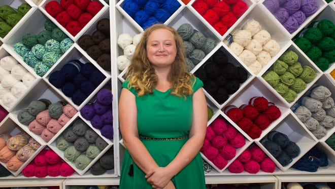 Emily Wagner, owner of My Yarn Stash in downtown Staunton, stands in front of a wall of yarn at the store on Wednesday, August 5, 2015. My Yarn Stash will be having their grand opening on Saturday at 11 a.m.