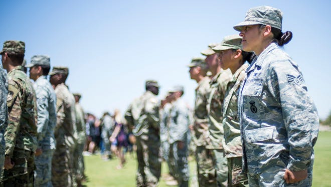 Senior Airman Lesley Trevizo stands at attention as she waits  to receive her Air Assault Badge. Trevizo is the first woman in the Air Force to graduate from the Fort Bliss Army Air Assault School, Iron Training Detachment.