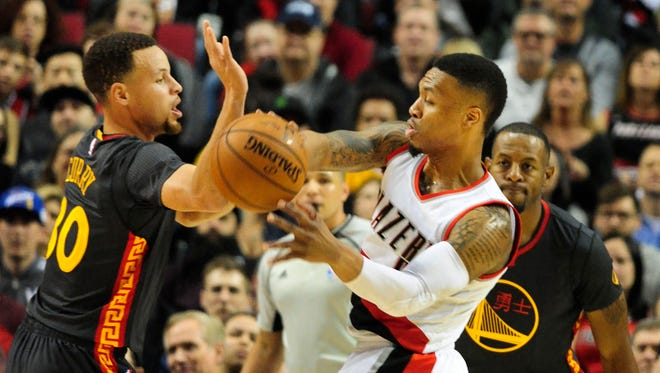 Portland Trail Blazers guard Damian Lillard (0) passes the ball on Golden State Warriors guard Stephen Curry (30) during the first quarter of the game at the Moda Center at the Rose Quarter.
