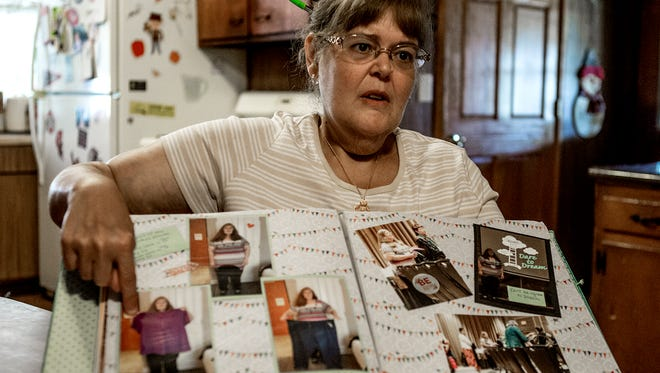 Dreama Hughes holds up a scrapbook with photos of her before she lost weight and holding up clothing she used to wear, Hughes has lost 174 pounds with the help of TOPS, a local support and information group for weight loss.