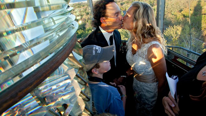Eric Decibus and Heather Rusczyk kiss after exchanging vows at the top of the Sandy Hook Lighthouse on Friday, Oct. 18, 2013, with Heather's sons Samson (wearing cap), 11, and Simon, 8, looking on.