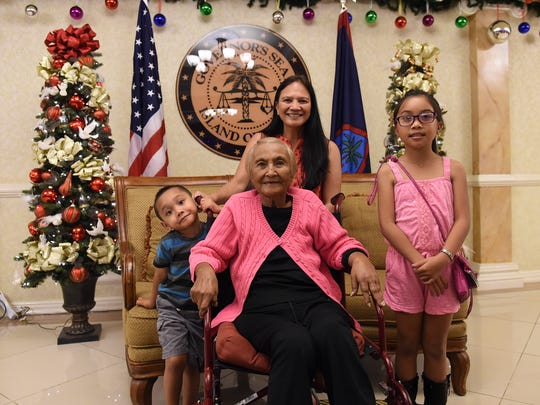 Connie Duenas, front center, a former mayor and vice mayor of Tamuning, with her family members Kathy Sulovski, top center, Robbie Mantanona, 3, left, and Shylie Leon Guerrero, 8, at the Government House on Dec. 2, 2017.