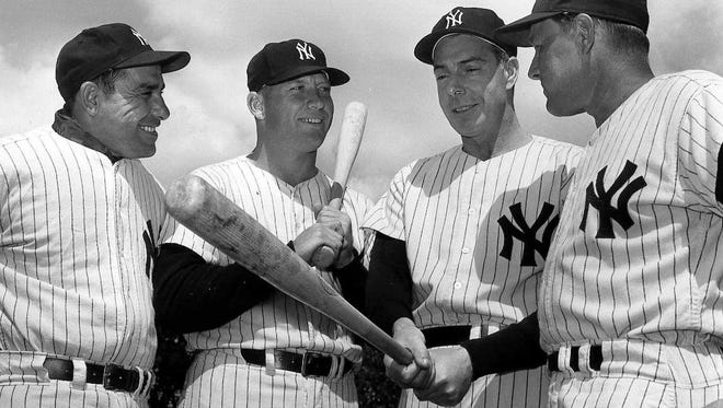 Baseball legend Joe DiMaggio, second from right, donned his uniform again to serve as an aide in spring traiing in this March 9, 1961 photo in St. Petersburg, Fla. From left are: Yogi Berra, Mickey Mantle, DiMaggio and manager Ralph Houk, who played on the Yankees when DiMaggio retired. DiMaggio, the elegant Yankee Clipper whose 56-game hitting streak endures as one of the most remarkable records in baseball or any sport, died Monday, March 8, 1999 at his home in Hollywood, Fla. He was 84.