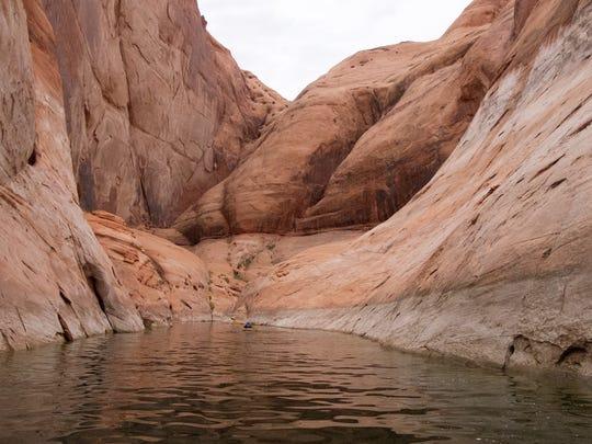 Ethan Burkett paddles a kayak up a narrow side canyon