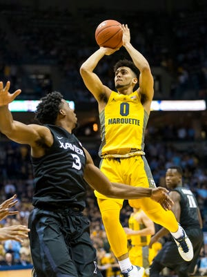 Marquette Golden Eagles guard Markus Howard shoots over Xavier Musketeers guard Quentin Goodin.