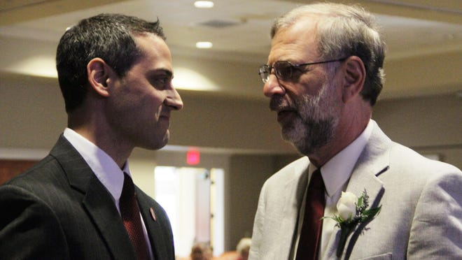 Sam Verghese, Secretary with the Florida Department of Elder Affairs, speaks with Dr. Sandy Halperin, right, about his work to find a cure for Alzheimer's disease.