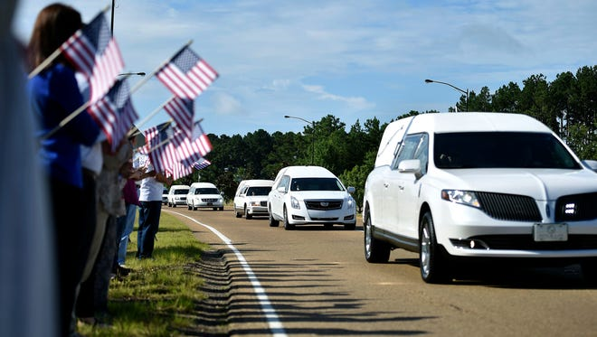 Supporters hold American flags on the side of Airport Road in Jackson, Miss., Thursday, July 13, 2017, as hearses carry the remains of the 16 service members who died in a plane crash in Leflore County, on Monday to the Air National Guard base for their final flights home.