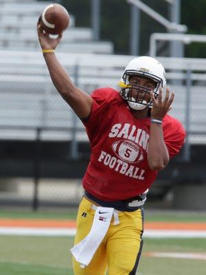 Saline senior quarterback Josh Jackson warms up before a scrimmage against Dearborn on Aug. 20, 2015.