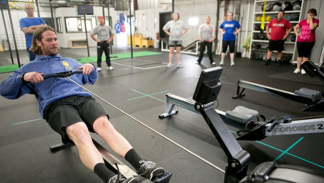 Owner and coach at Fiternal CrossFit James Jernberg demonstrates a row machine during a class in Stevens Point, Monday.