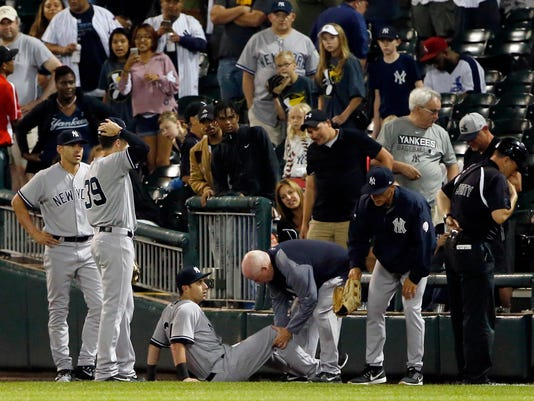 FILE - In this June 29, 2017, file photo, New York Yankees' Dustin Fowler is checked by a team trainer after an injury during the first inning of the team's baseball game against the Chicago White Sox in Chicago. The Oakland Athletics' likely center fielder of the future didn't know anybody Tuesday, a day after being traded by the Yankees in the deal that sent Sonny Gray to New York. As Gray's news conference in the Bronx showed on the A's clubhouse TV with his former teammates tuning in, Fowler discussed his own journey West. (AP Photo/Nam Y. Huh, File)