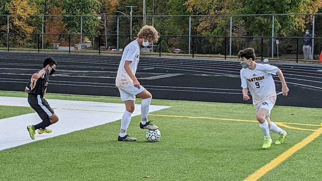 Quabbin senior William Ordung, center, plays a short corner kick from teammate Matthew Marsh (9) in front of Gardner defender Henry Aguilar during the season-opening contest between the Panthers and the Wildcats at Watkins Field earlier this month.