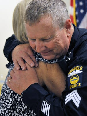 Lieutenant Dan Martincin gets a hug from his wife Kim during his promotion ceremony at the Mansfield Police Department Monday.