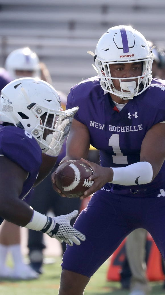 New Rochelle quarterback Jonathan Saddler hands off