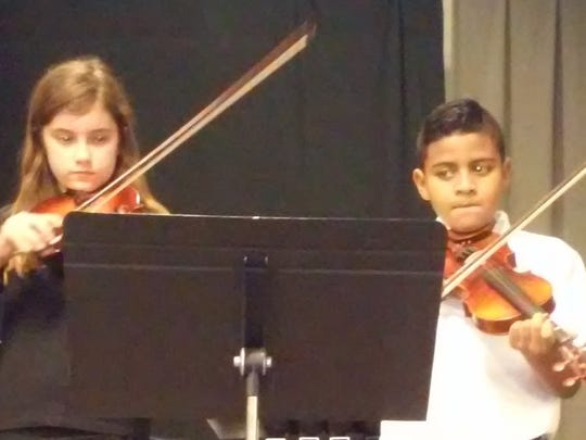 Sixth-grade violinists Madeleine Dionne and Mateo Angulo prepare to play.