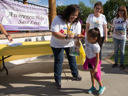 Adrianna Peña reaches into the bin to select a raffle winner as CARE Executive Director Yolanda Rigales Diaz assists her at the Race for CARE 5K Run/1K Walk held on National Cancer Survivors Day, June 4, 2017.