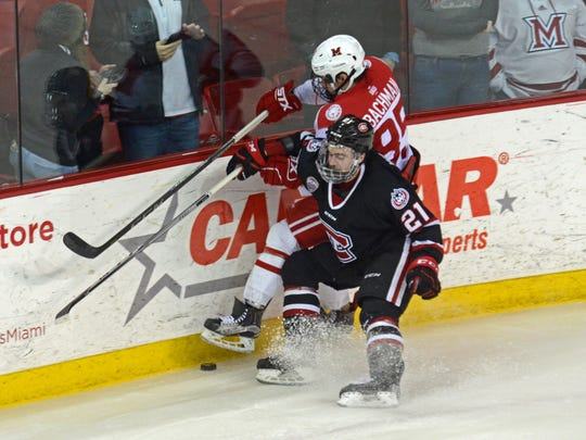 St. Cloud State's Jake Wahlin (21) battles Miami's