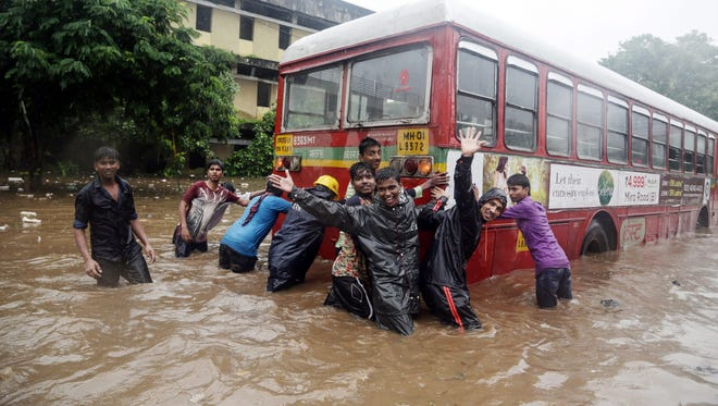 Indian people pushes a public transport bus as it stop functioning in a water logged area in Ghodbunder on the outskirts of Mumbai, India, 31 July 2016.