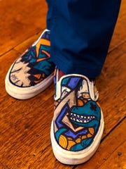 Harry Mack Truax II wears Vans skateboard shoes hand-painted with dinosaurs by Timmy Hamm.