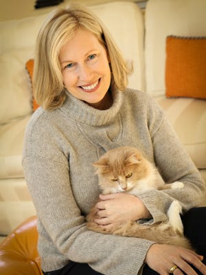 Brenda Heckert wears a Garnet Hill light gray cashmere cable turtleneck sweater; Banana Republic long-sleeve white cotton crew neck; dark denim James jeans from Ellie Boutique; and her cat Mimi.