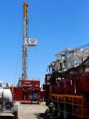 A idle workover rig sits in the rig yard of Aztec Drilling on Thursday in Aztec.
