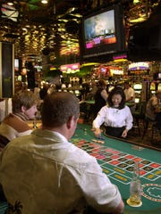 Gambling continues unabated at Fitzgerald's in downtown Reno Tuesday afternoon, as monitors show the news about the terrorist attacks at the World Trade Center and the Pentagon. Playing roulette are Doris and Ken Denney of San Diego as Stanza So deals.