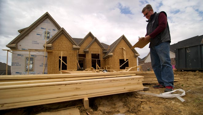 Scott Krahl, with Jim Krahl Builders, works on a materials inventory at a job site on Briarton Drive in Southaven, Miss., in March 2014.