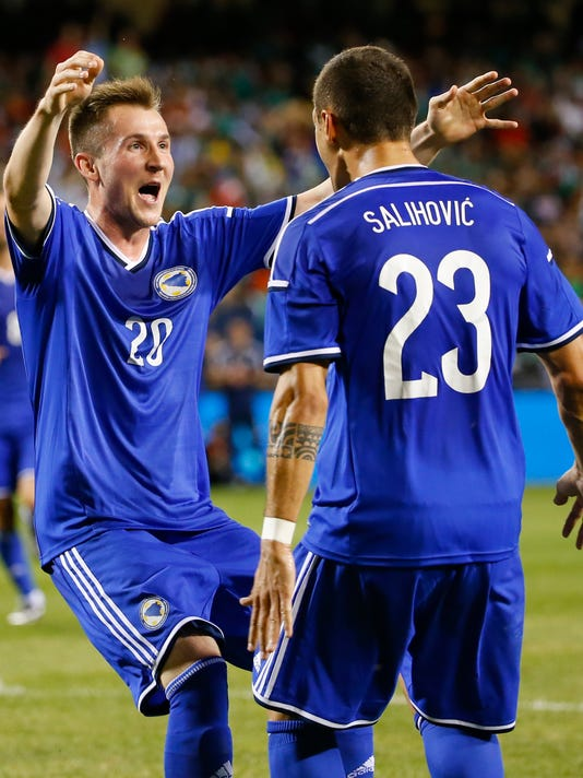 Bosnia-Herzegovina forward Izet Hajrovic (20), celebrates after scoring against Mexico, with midfielder Sejad Salihovic (23) during the first half of an international friendly soccer match at Soldier Field in Chicago, Tuesday, June 3, 2014. (AP Photo/Kamil Krzaczynski)