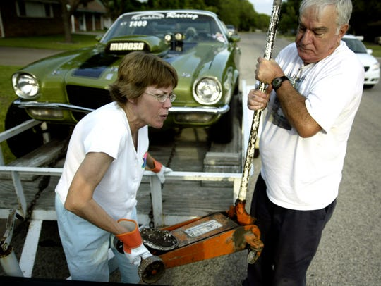 Betty Taylor helped her husband, George Taylor, load a jack into their pickup truck on July 15, 2005, as they load up George's 1970 Camaro before drag racing the next day.
