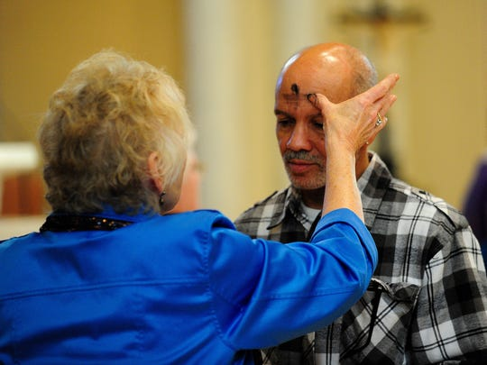 Sandra Matthieu uses ashes to mark a cross on the forehead of Al Thomas during an Ash Wednesday Mass at St. Genevieve Roman Catholic Church in Lafayette on March 5, 2014. Ash Wednesday marks the beginning of Lent.