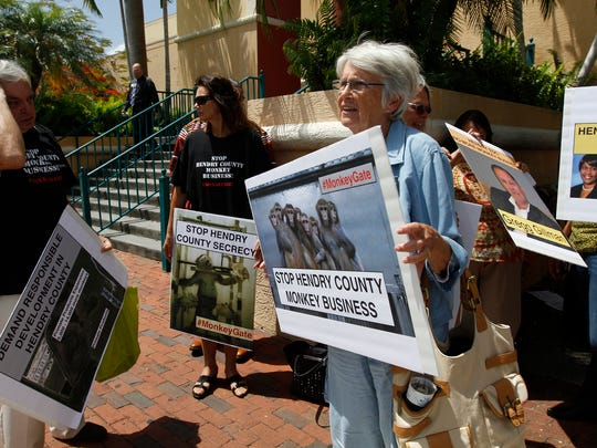 Protester Pam Cross, center, brings attention to Hendry County monkey farms after the Market Watch Regional Economic Development Summit in Fort Myers Monday.