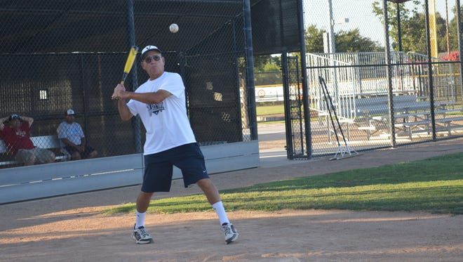 Visalia coach Frank Durazo hits the ball during baseball practice at Riverway Sports Park.