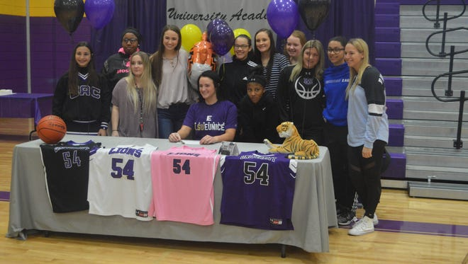 University Academy's Jordyn Cross (center) poses with teammates during her signing to LSU of Eunice on Friday.