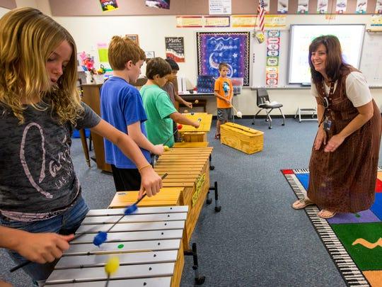 Music teacher Rene Suderman guides fifth graders, including