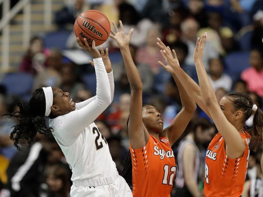 Notre Dame's Arike Ogunbowale (24) shoots against Syracuse's Kiara Lewis (12) and Miranda Drummond (32) during the first half of an NCAA college basketball game in the Atlantic Coast Conference women's tournament in Greensboro, N.C., Saturday, March 9, 2019. (AP Photo/Chuck Burton)
