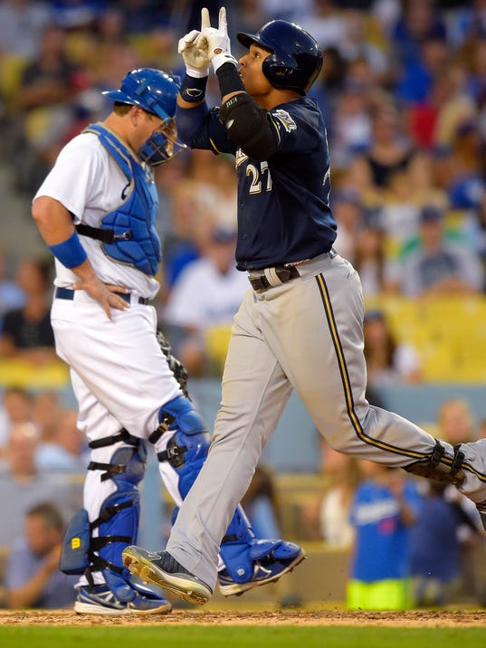Milwaukee Brewers' Carlos Gomez, right, scores on his solo home run, as Los Angeles Dodgers catcher A.J. Ellis waits during the sixth inning of a baseball game, Saturday, Aug. 16, 2014, in Los Angeles. (AP Photo/Mark J. Terrill)
