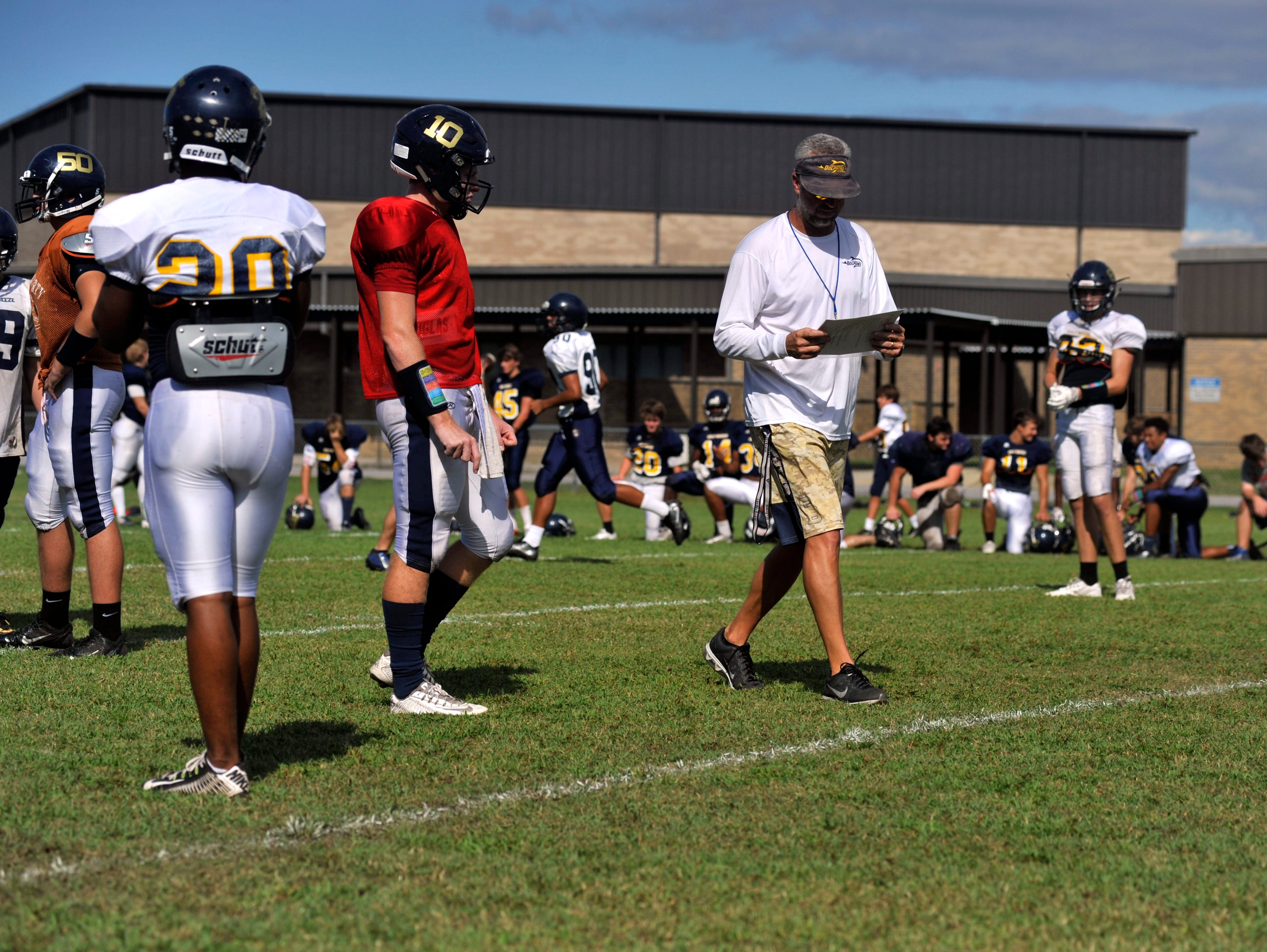 Gulf Breeze head coach Bobby Clayton calls plays for senior quarterback Tyler Phelps (No. 10) during practice on Sept. 14, 2016.