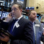 Trader Fady Tanois, left, works on the floor of the New York Stock Exchange, Tuesday, Jan. 12, 2016.   (AP Photo/Richard Drew)