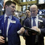 Specialist William McArdle, left, and trader Patrick Casey, right, work on the floor of the New York Stock Exchange, Wednesday, Jan. 27, 2016. Stocks are opening broadly lower as energy companies take another tumble and after Apple predicted its first sales decline in 13 years. (AP Photo/Richard Drew)