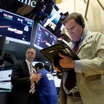 Trader Jonathan Niles, right, works on the floor of the New York Stock Exchange, Wednesday, March 30, 2016.  (AP Photo/Richard Drew)