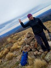 Anna Dozier stands near Nogal Peak trail with a back