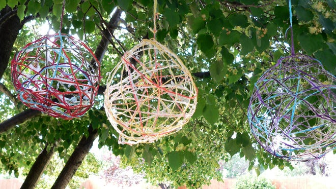 Colorful orbs — made from glue-soaked yarn wrapped around balloons — hang in a tree in Arvada, Colo. This and other crafts were featured at a teen crafting party.