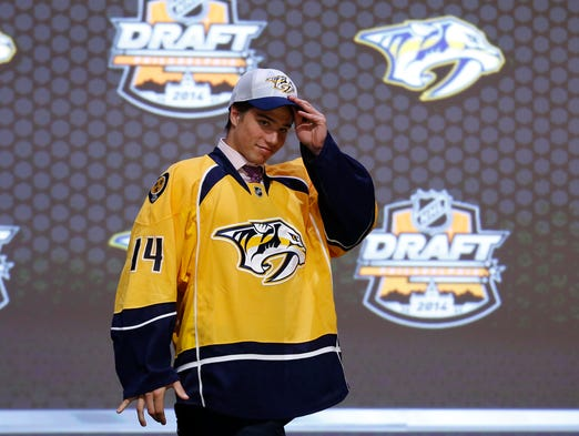 Kevin Fiala walks off the stage after being chosen 11th overall by the Nashville Predators during the first round of the NHL hockey draft, Friday, June 27, 2014, in Philadelphia.
