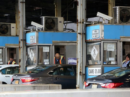 Toll booth workers collect money from drivers at the