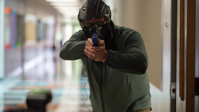 An educator partakes in a simulated shooting as part of a training for school marshals. School marshals are school staff trained and armed to take out a threat to their campus.