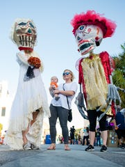 Avery Lindsey, 6 months, and Danielle Lindsey pose for a photo with Monos de Calenda, or puppets of the procession, produced by K-Space on Saturday, Oct. 29, 2016, during the Día de los Muertos Street Festival in downtown Corpus Christi. The Corpus Christi Hooks are hosting a celebration emulating Dia de los Muertos over Memorial Day weekend.